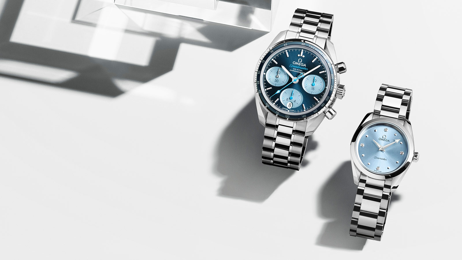 Two Omega watches side by side with stainless steel cases and bracelets and blue dials